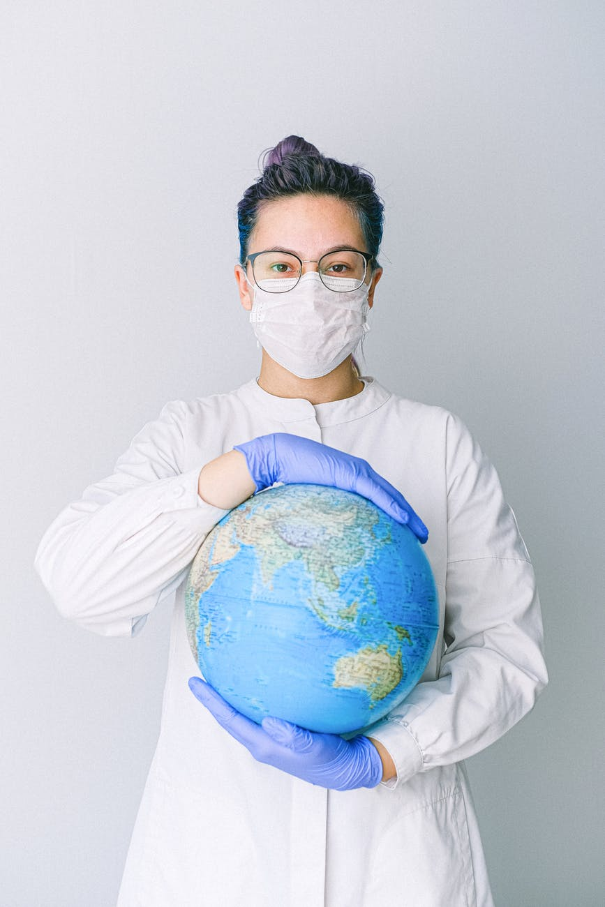 person with a face mask and latex gloves holding a globe